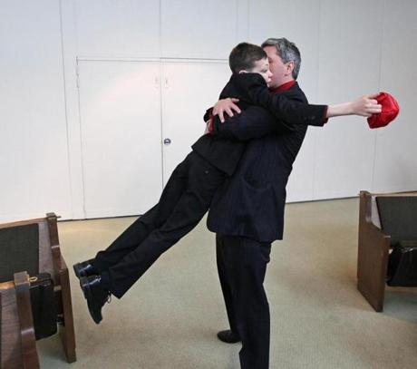 Andover, MA 030312 Matthew Emi (Cq) jumps into his father's, Michael Emmi (Cq) arms after his bar mitzvah. Since Matthew couldn't recite all the prayers and blessings he used an iPad during the ceremony which took place on March 3, 2012 at Temple Emanuel. (Essdras M Suarez/ Globe Staff)/ MET